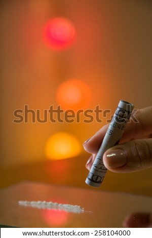 Woman's hand with one hundred US dollars note to use cocaine . - stock photo
