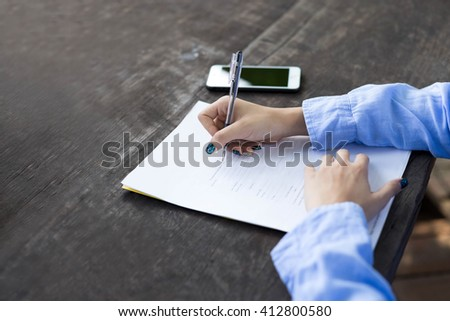 woman's hand with pen completing application form on wooden table - stock photo