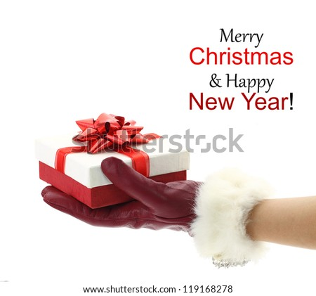 Woman's hand with red glove holding a Christmas gift - stock photo