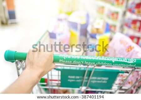 Woman 's hand with shopping cart in supermarket - stock photo