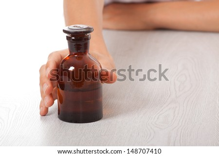 woman's hand with small bottle - stock photo