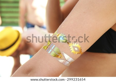 Woman's hand with sticker tatoo outside on the pool - stock photo
