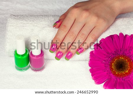 Woman's hand with two-color manicure in salon - stock photo