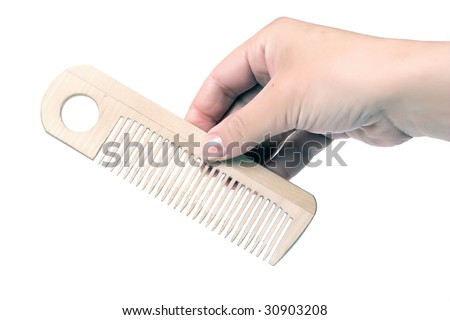 Woman's hand with wooden comb isolated on white.