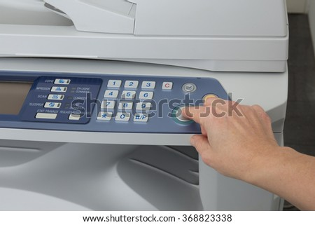 Woman's hand with working copier isolated on white - stock photo