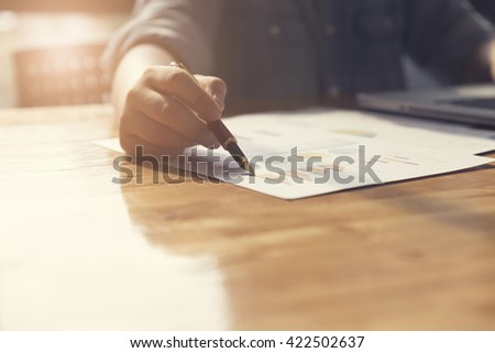 woman's hand working with business document and laptop computer notebook for working concept, selective focus and vintage tone