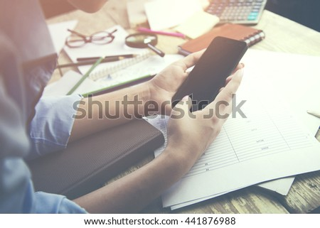 woman's hand working with mobile phone, business document, working concept on table
