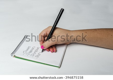 woman's hand writing a list of vegetables on white background - stock photo