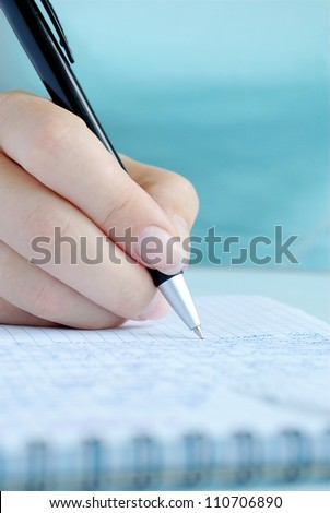 woman's hand writing entries in a notebook - stock photo