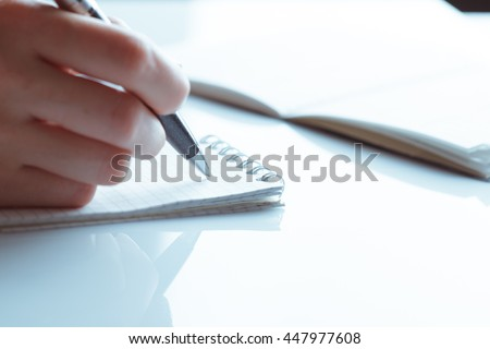 woman's hand writing entries in a notebook. studio shot - stock photo