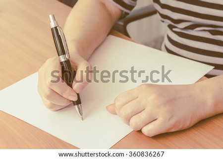 woman's hand writing on paper
