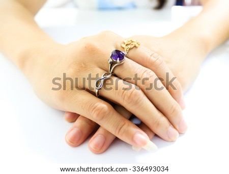 Woman's hands are wearing rings - silver ring, amethyst ring, and golden ring