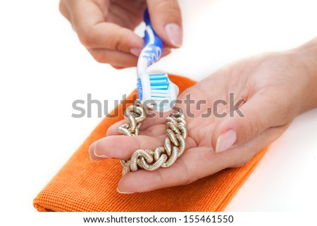 Woman's hands cleaning golden bracelet with a toothpaste - stock photo