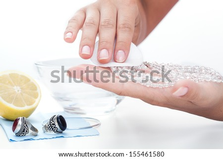Woman's hands cleaning jewellery with a lemon juice - stock photo