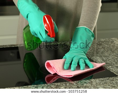 Woman's hands cleaning kitchen top in gloves - stock photo