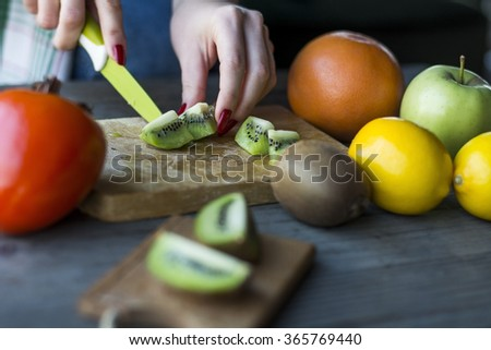 Woman's hands cuts fresh kiwi fruit  - stock photo