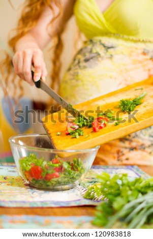 Woman s hands cutting fresh onions, dill, parsley on kitchen Focus on green vegetables The concept of food and a healthy lifestyle - stock photo