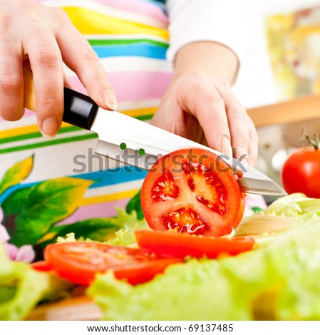 Woman's hands cutting tomato, behind fresh vegetables.