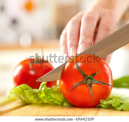 Woman's hands cutting tomato, behind fresh vegetables. - stock photo