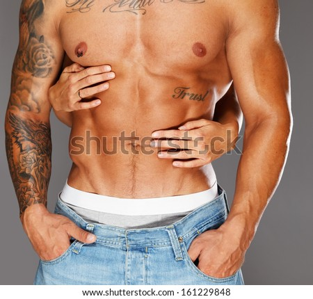 Woman's hands embracing man with naked muscular torso  - stock photo