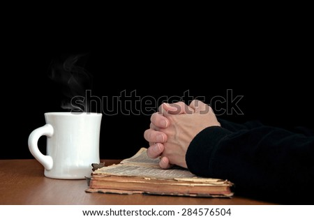 woman's hands folded in prayer on a worn vintage Bible with white coffee mug - stock photo