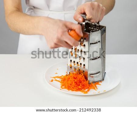 Woman's hands grating carrot - closeup shot - stock photo