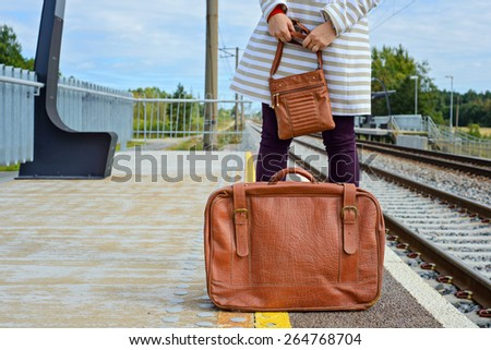 Woman's hands holding a brown bag and vintage suitcase at train station - stock photo