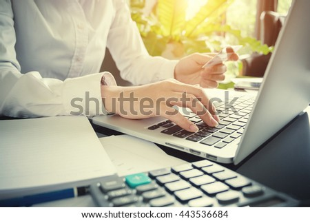 Woman's hands holding a credit card and using laptop for online shopping or online payment - stock photo