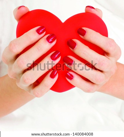 Woman's hands holding big red heart - stock photo