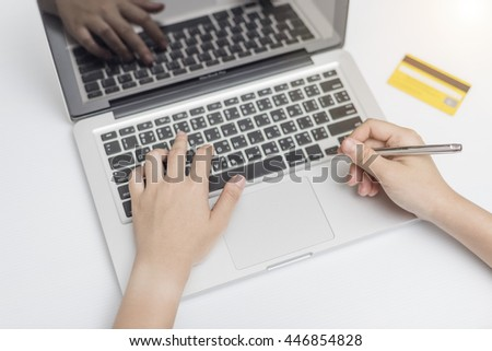 Woman's hands holding credit card and using laptop for online shopping.