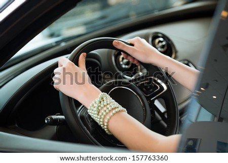 woman's hands holding on to the wheel of a new car in the showroom - stock photo