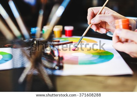 Woman's hands holding orange paint and brush, pencils, drawings and glasses on dark wooden table, copy space.