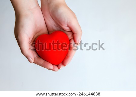 Woman's hands holding sweet red heart - stock photo