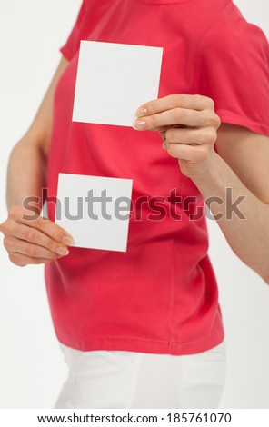 Woman's hands holding two blank white stickers over bright red t-shirt - stock photo