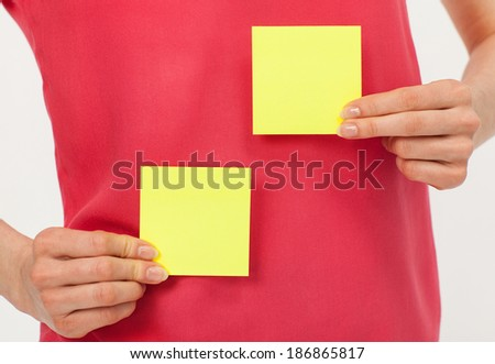Woman's hands holding two blank yellow stickers over bright red t-shirt