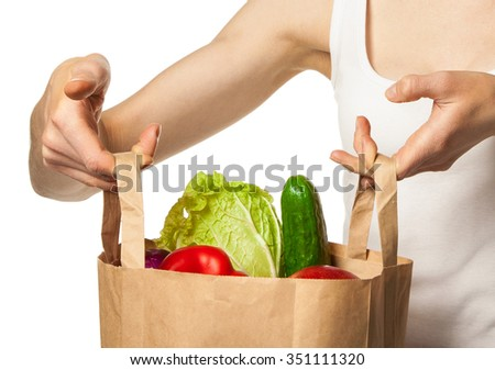 Woman's hands holding vegetables and fruits in shopping bag - stock photo
