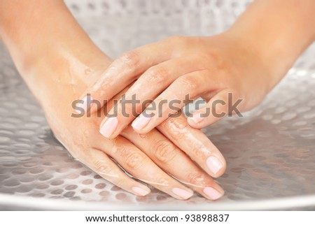 Woman's hands humidification in the sink with water