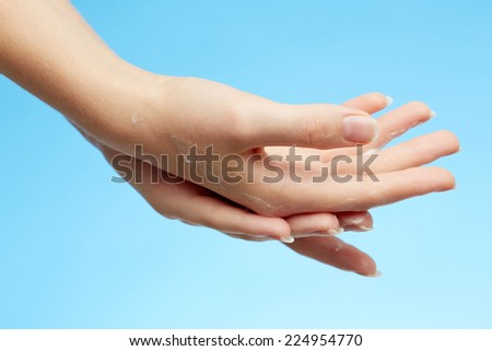 Woman's hands in moisturizer cream on blue background - stock photo
