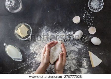 Woman's hands knead dough on table with flour and ingredients. Top view. - stock photo