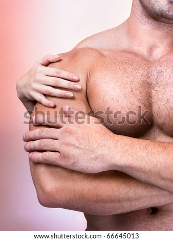 Woman's hands on a sexy man's torso, studio shot