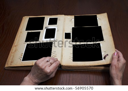 woman's hands on an old vintage photo album