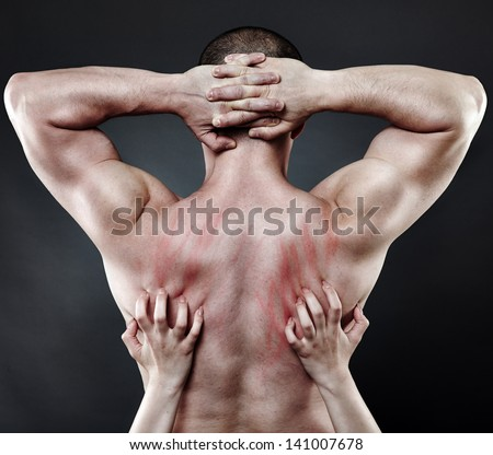 Woman's hands plunging her nails into her muscular partner's back - stock photo