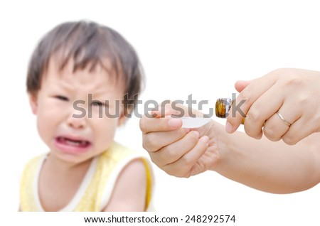 Woman's hands pouring medicine in a spoon foreground and  crying baby sitting in background - stock photo