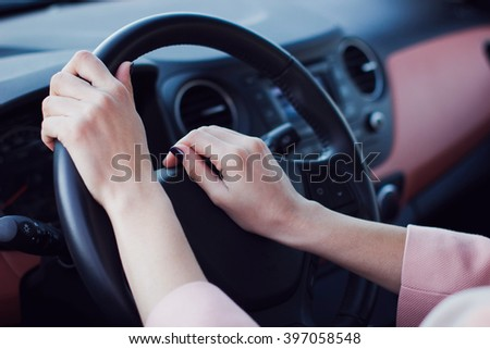 Woman's hands pushe the button on a steering wheel in car