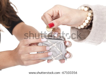 woman's hands putting a coin on a silver purse