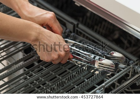 Woman's hands putting forks, spoons and knives in the cutlery compartment of a dishwasher, preparing to do the dishes