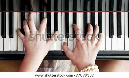 Woman's hands striking a chord on the keys of a black lacquered piano