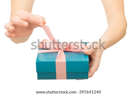 woman's hands unboxing giftbox with bow. untie bow - stock photo