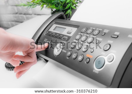 Woman's hands using fax