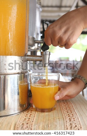 woman's hands were pressing orange juice into drink glass in a restaurant.